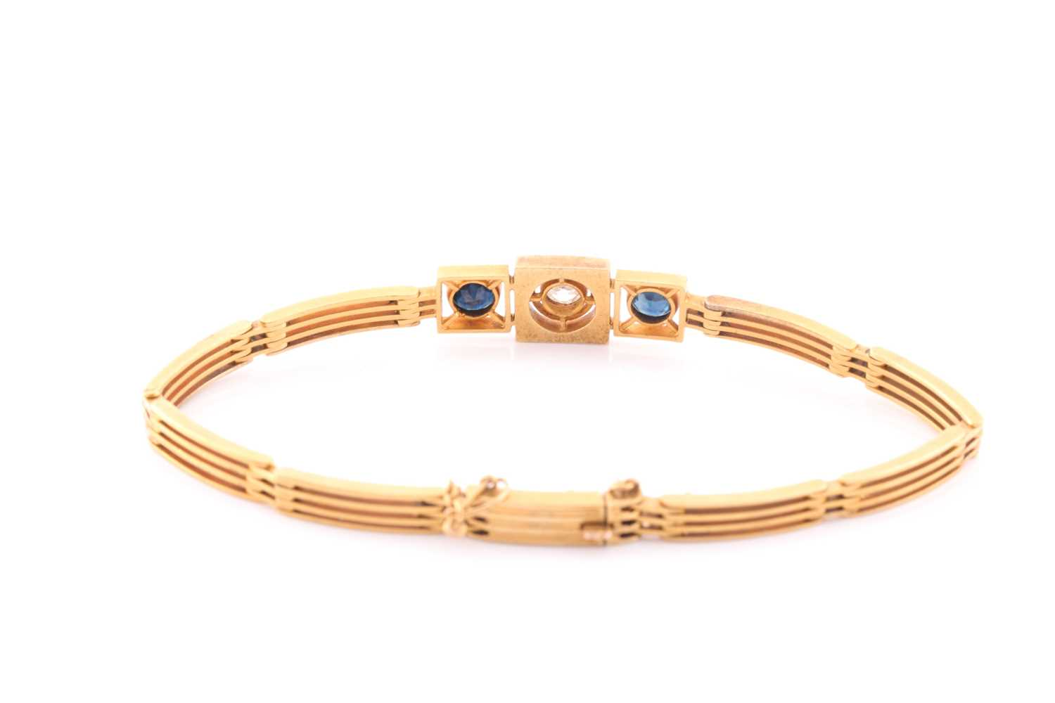 A yellow metal, diamond, and sapphire bracelet, set with a round-cut diamond of approximately 0.33 - Image 5 of 5