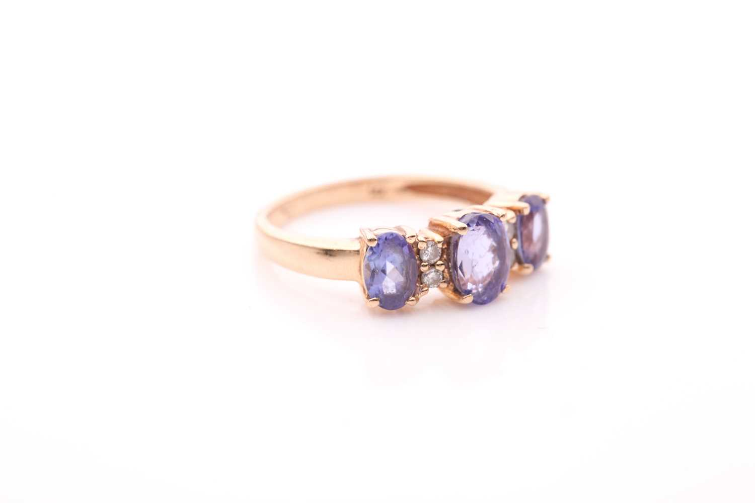 A yellow metal and tanzanite ring, set with three mixed oval-cut tanzanites, interspersed with - Image 5 of 5
