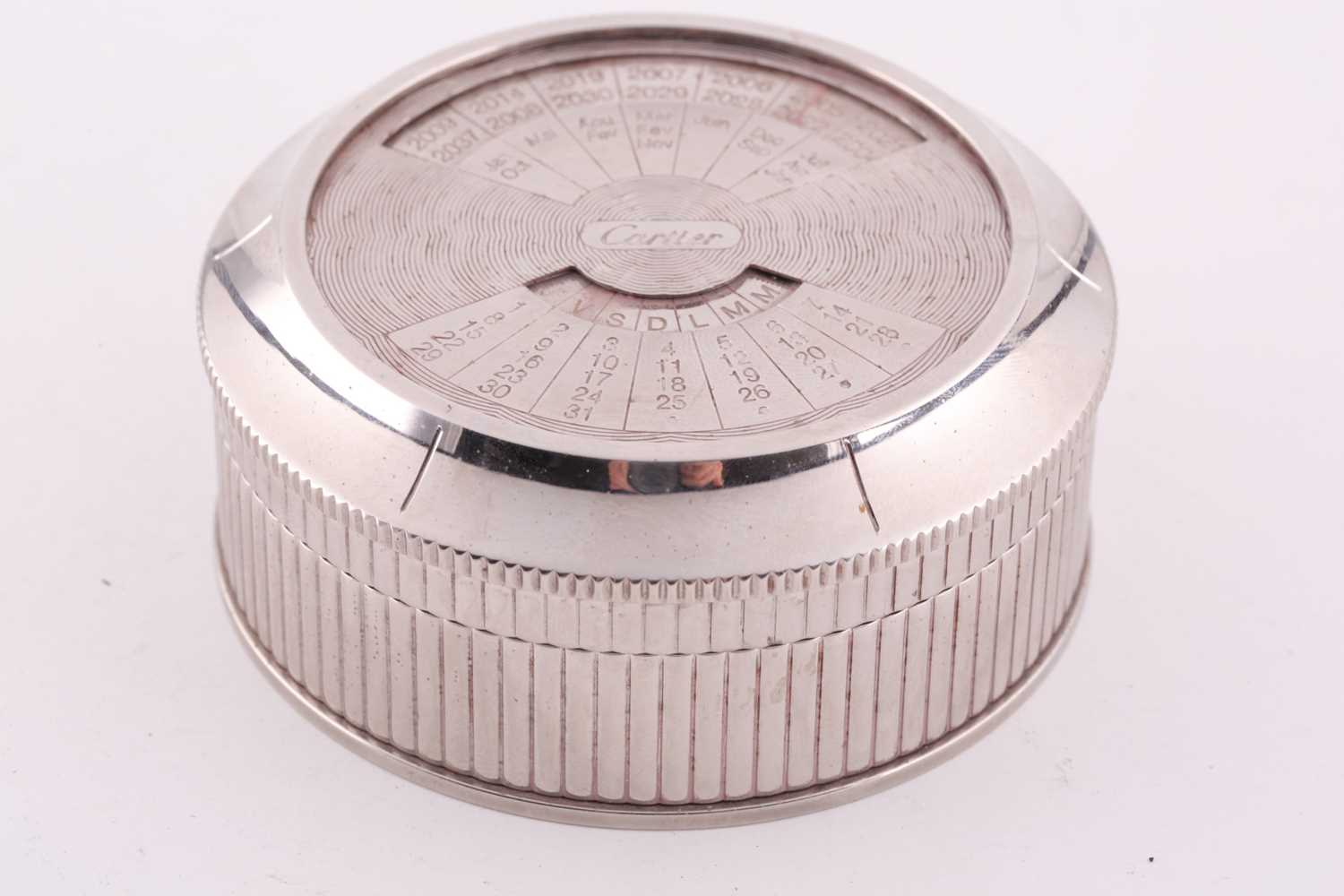 A Cartier chrome desk calender, with adjustable year, month, and date dial to lid, 8 cm diameter, - Image 3 of 5