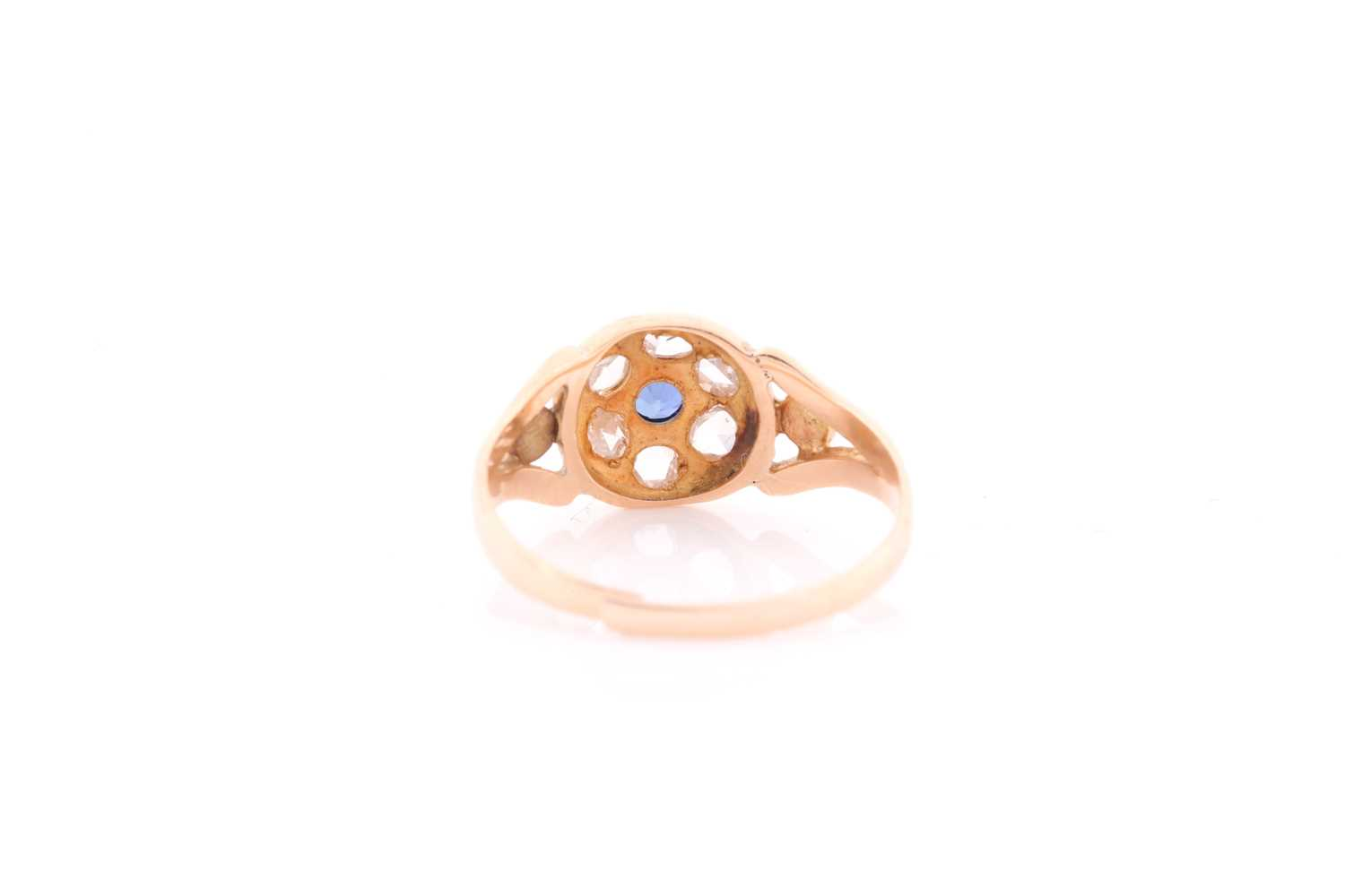 A yellow metal, diamond, and sapphire ring, set with a small round sapphire, within a border of - Image 3 of 4