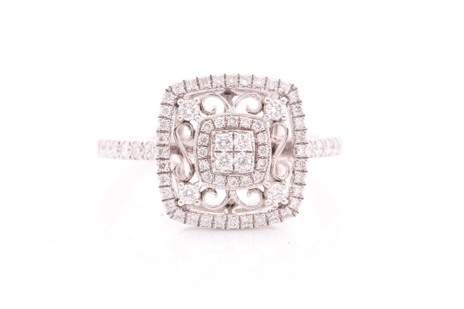 An 18ct white gold and diamond ring, the openwork mount with filigree style decoration, inset with