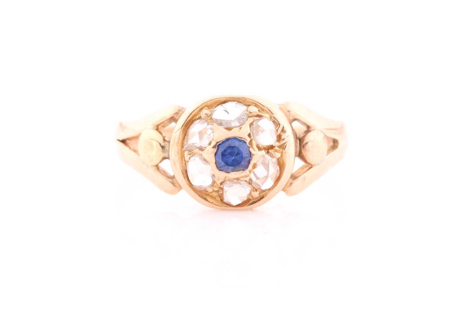 A yellow metal, diamond, and sapphire ring, set with a small round sapphire, within a border of