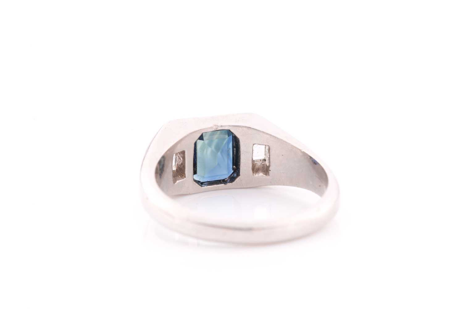 A diamond and sapphire ring, set with a mixed rectangular-cut sapphire, flanked with two modified - Image 3 of 4