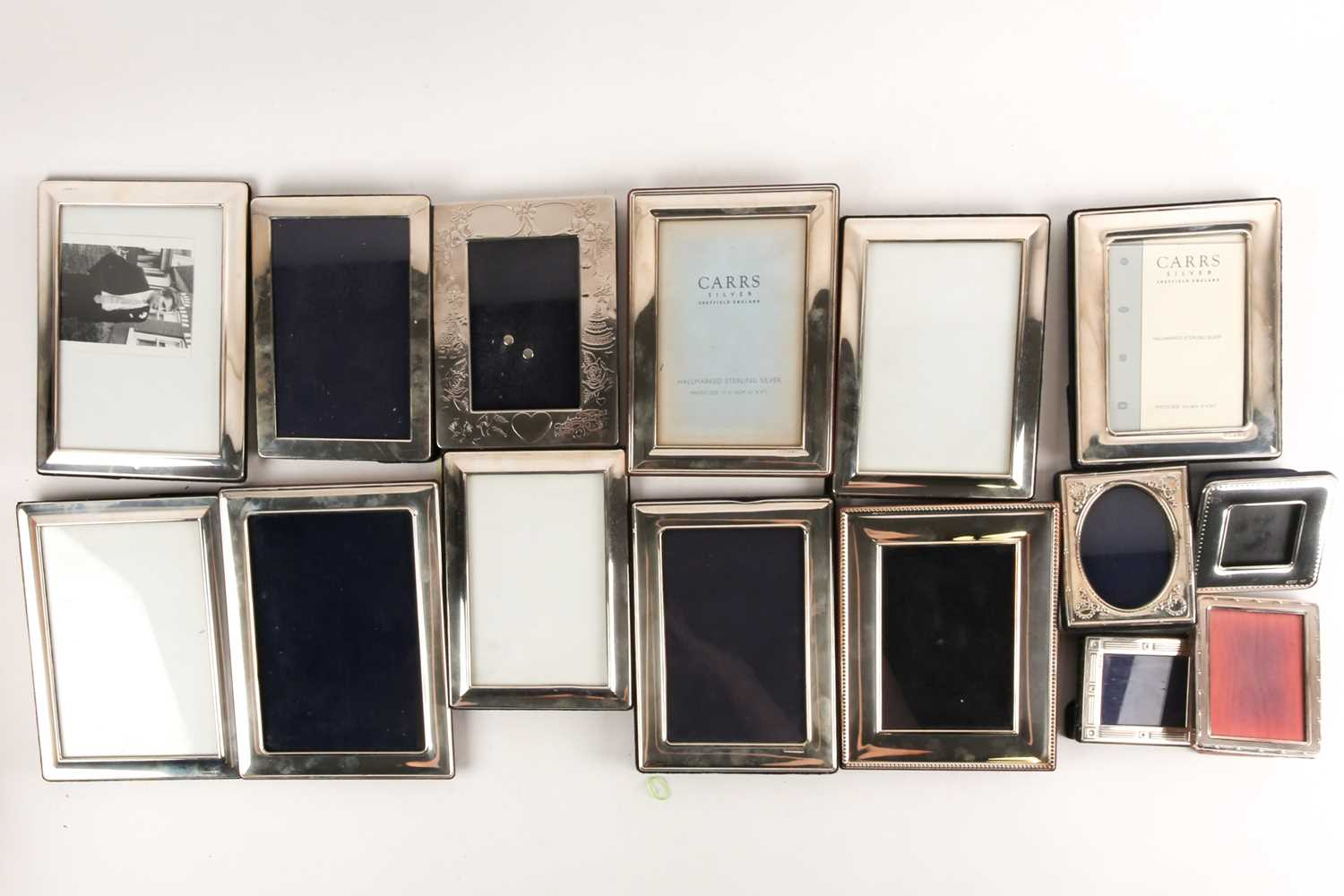 A large collection of silver and white metal mounted photograph frames, the largest aperture size