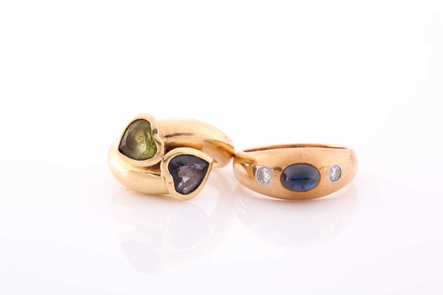 An 18ct yellow gold gypsy ring, set with a cabochon sapphire and two small diamonds, size M,