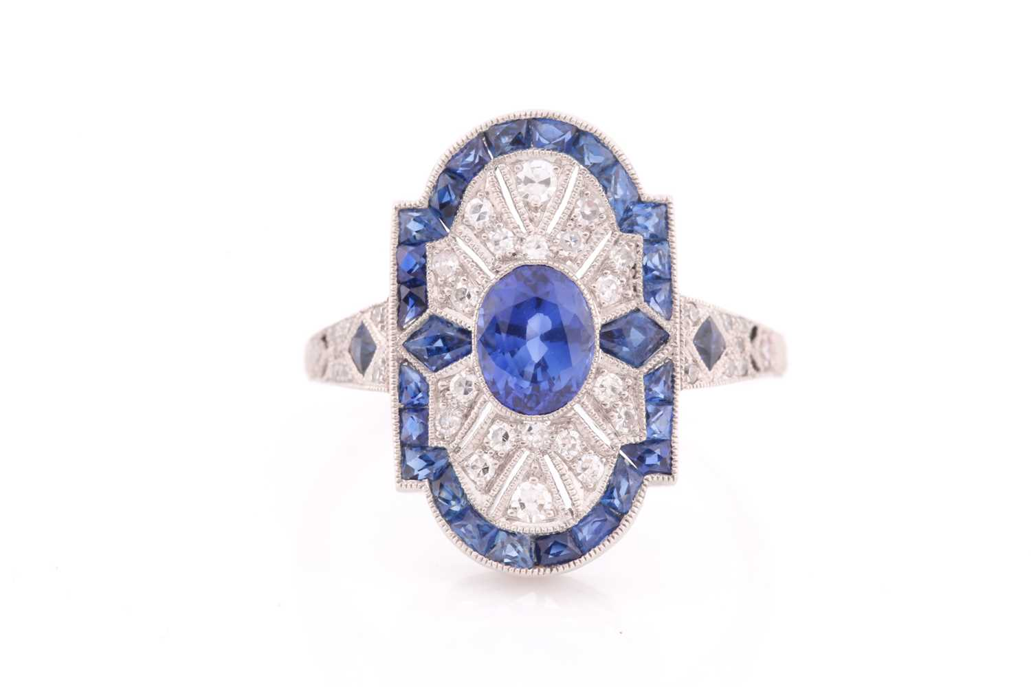 A platinum, diamond, and sapphire plaque ring, in the Art Deco style, centred with a mixed oval-