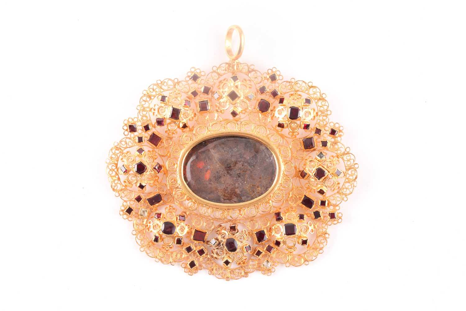 A Catalan gold and garnet pendant, centered with an oval glass aperture with faded paint, within
