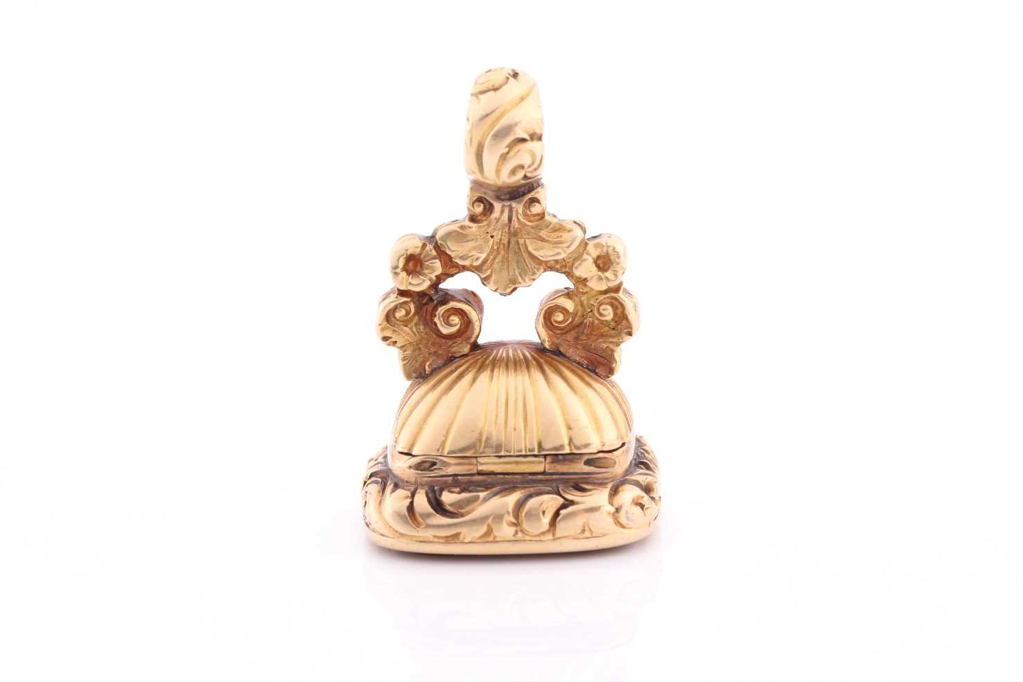 A yellow metal and red agate fob seal, with concealed locket, hinged base, unmarked (tests as 15ct