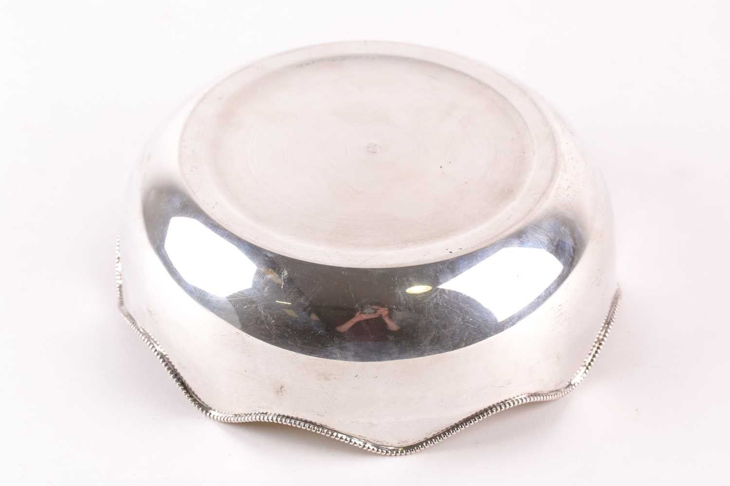 A 20th-century circular white metal fruit bowl with a serpentine beaded rim. Bearing indistinct - Image 4 of 4