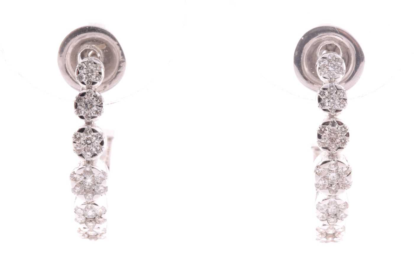 A pair of 18ct white gold and diamond earrings, each set with seven graduated floral clusters of
