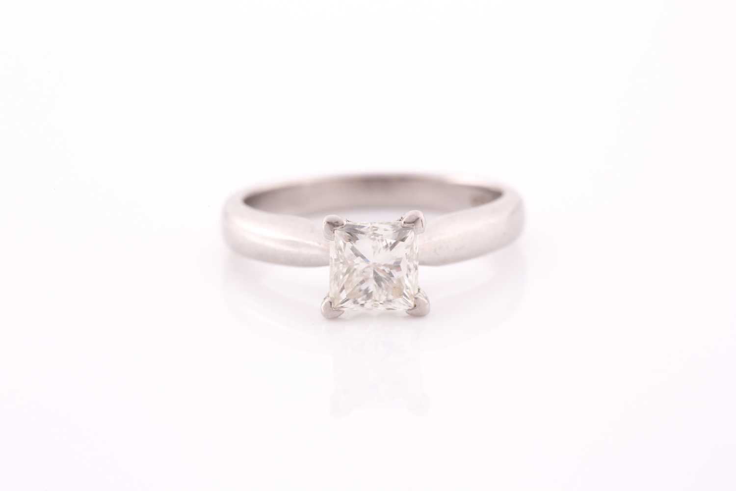 A platinum and diamond ring, set with a princess-cut diamond of approximately 0.80 carats,