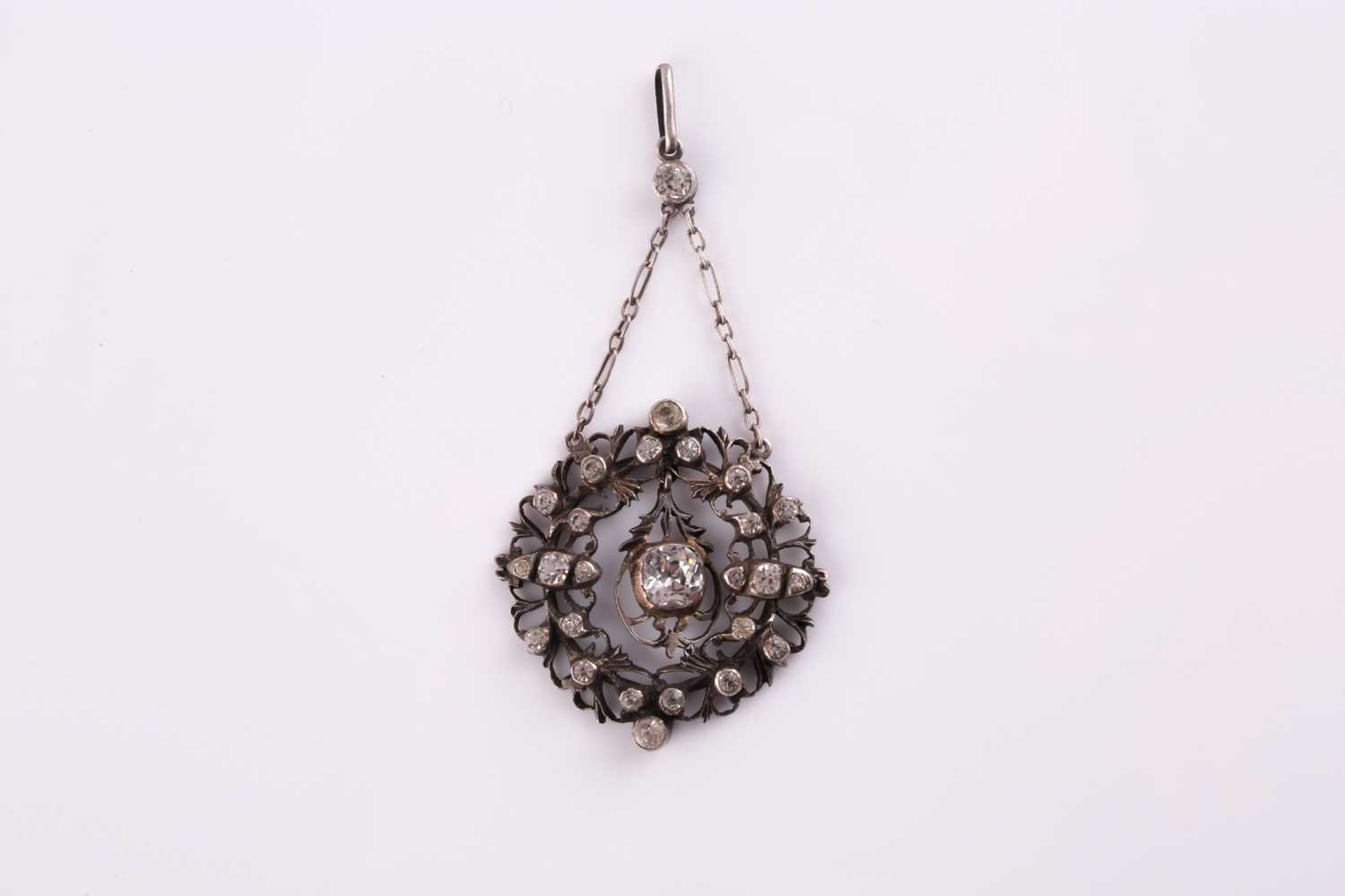 A 19th century white metal and paste pendant, centered with a cushion-cut paste pendant, the