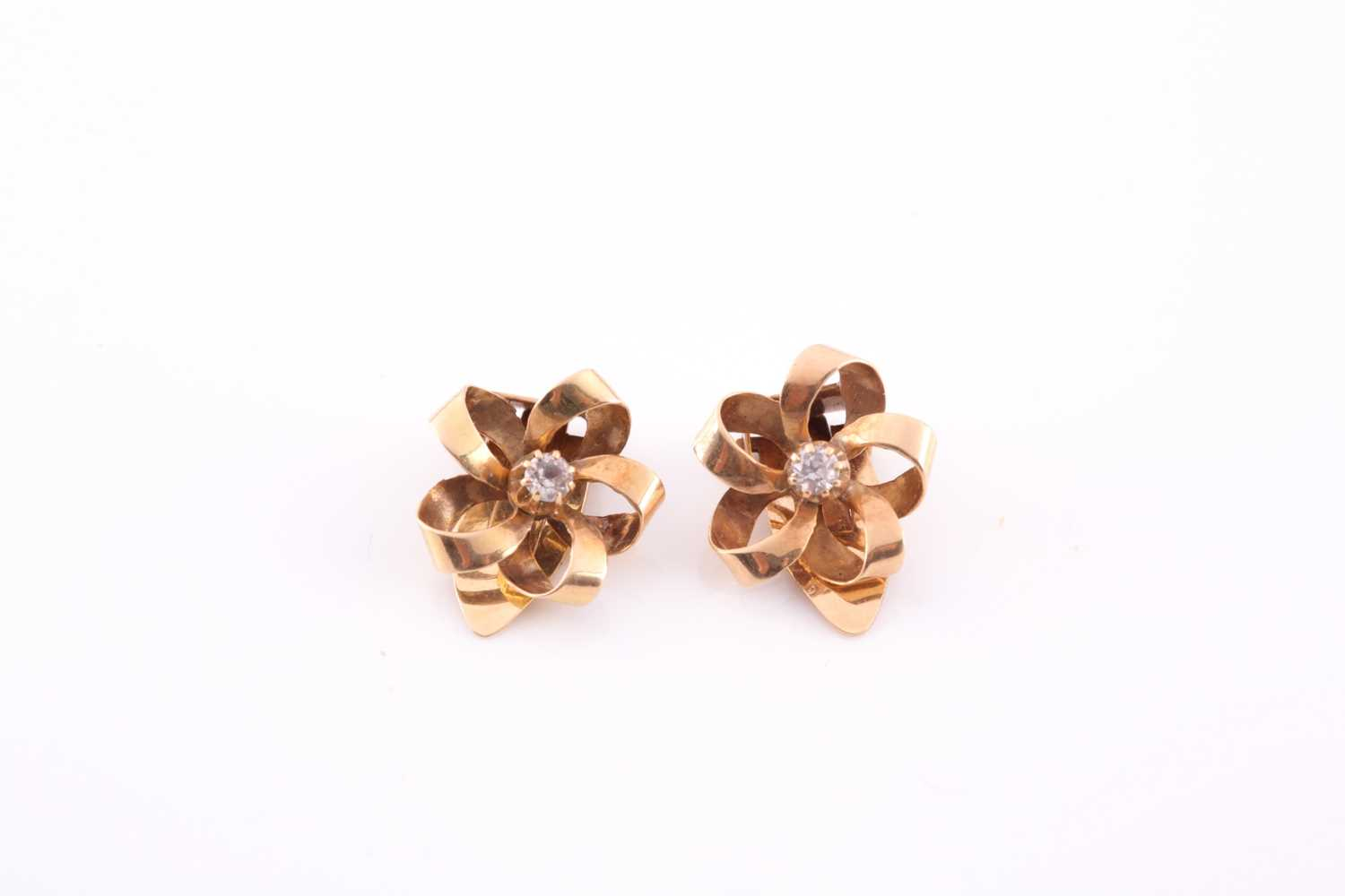 A pair of yellow metal ribbon-twist earrings, each centred with a small white stone, marked 585,