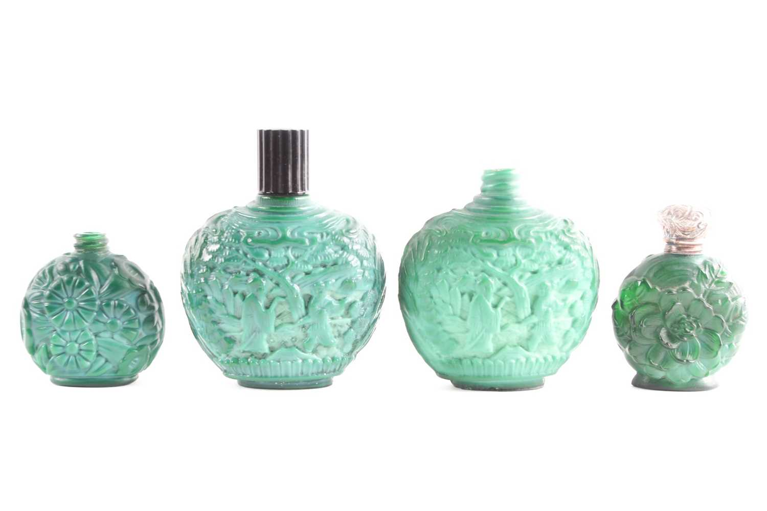 A collection of four carved and moulded green glass scent bottles; carved with scenes from rural