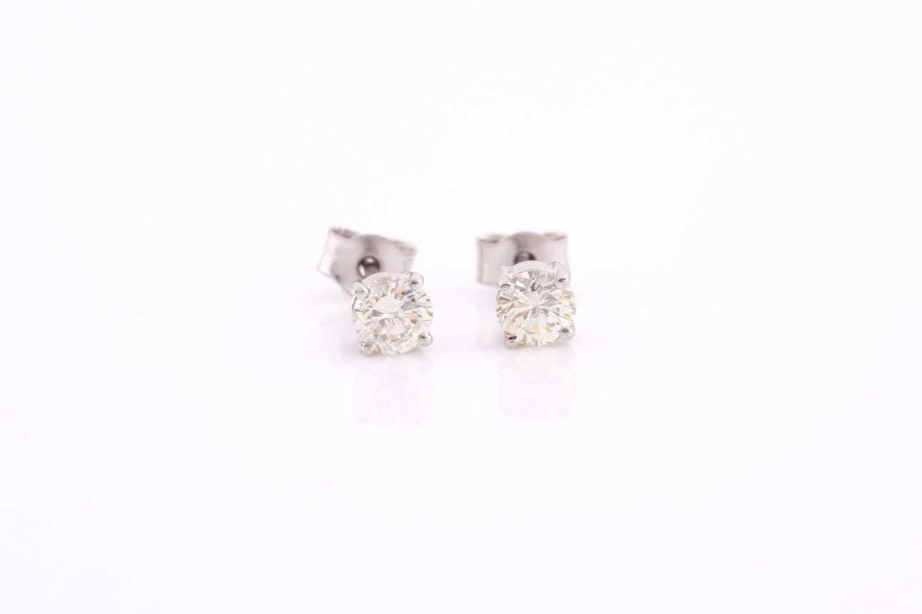 A pair of platinum and diamond earrings, the round brilliant-cut diamonds of approximately 0.67
