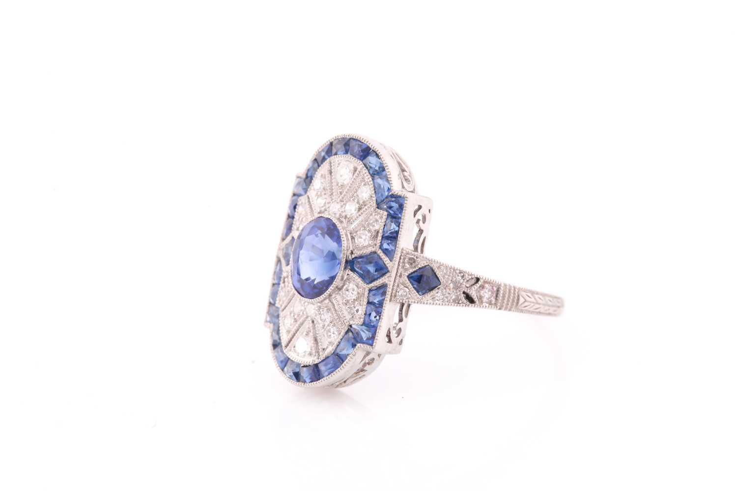A platinum, diamond, and sapphire plaque ring, in the Art Deco style, centred with a mixed oval- - Image 2 of 4