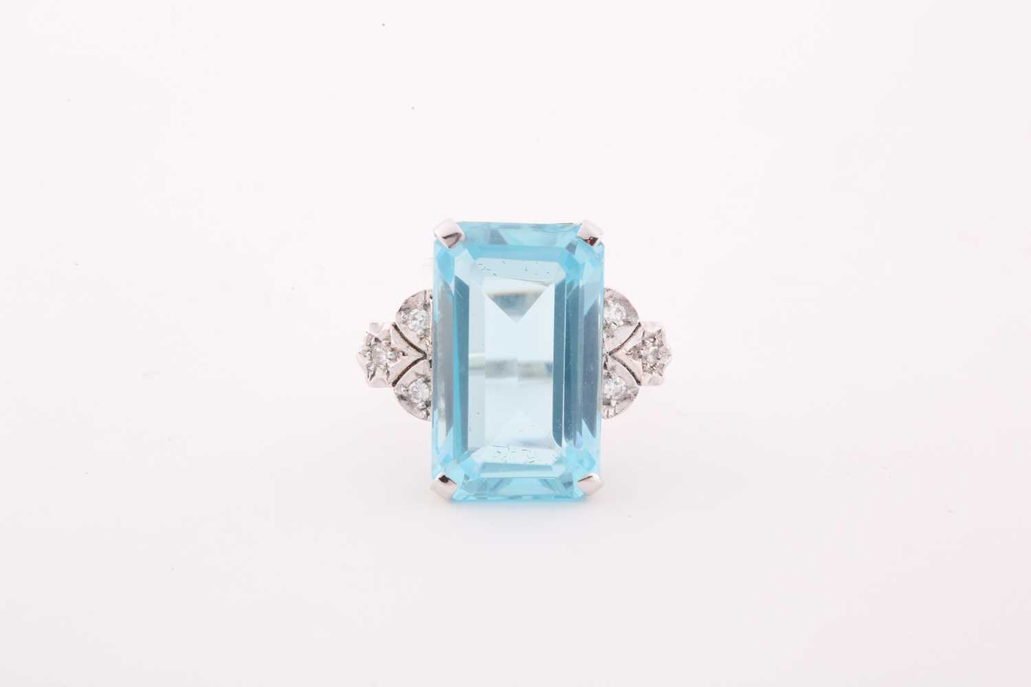 A diamond and blue topaz cocktail ring, set with a mixed rectangular-cut topaz, measuring