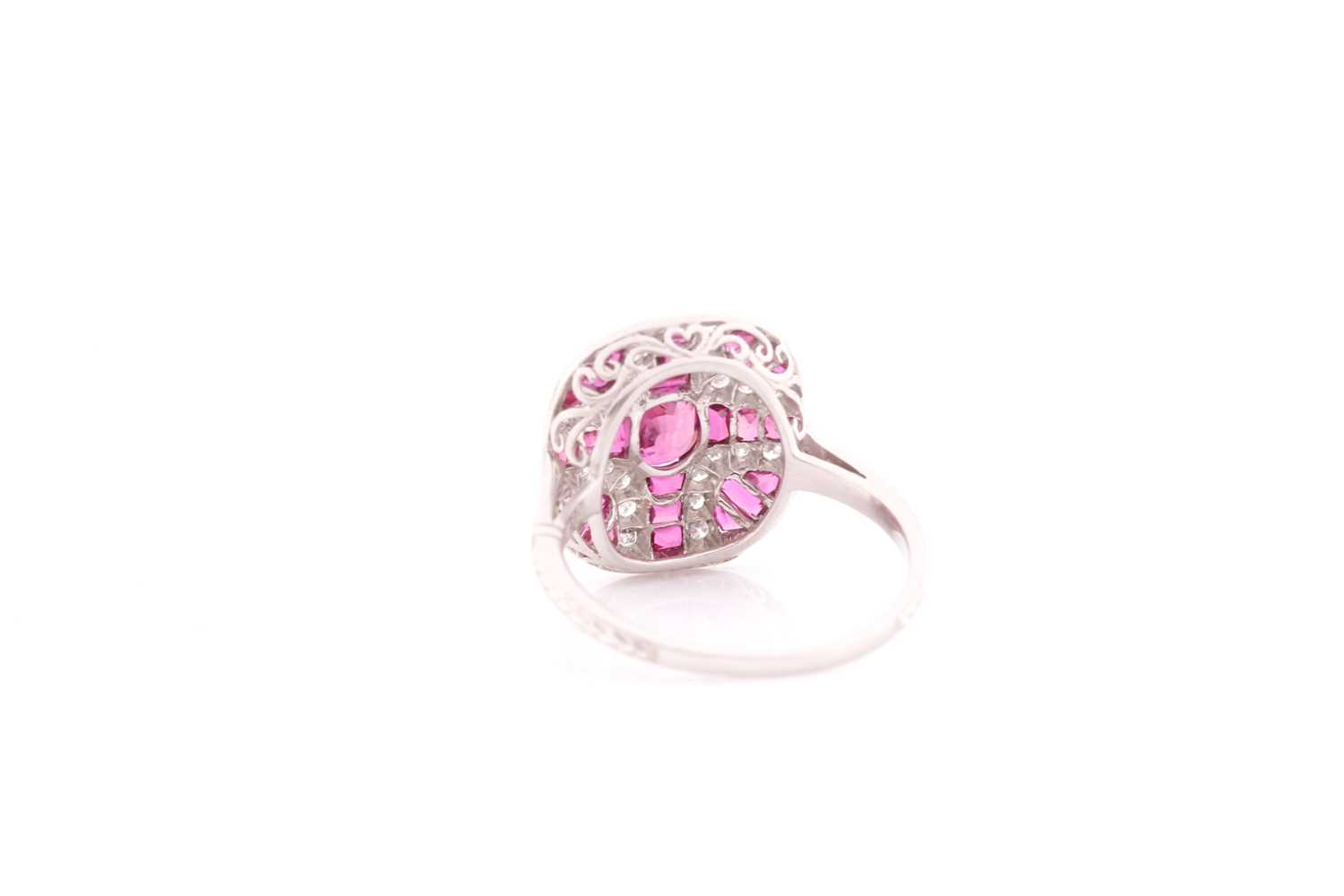 A platinum, diamond, and ruby ring, the rounded mount calibre-set with a mixed oval-cut ruby - Image 3 of 4