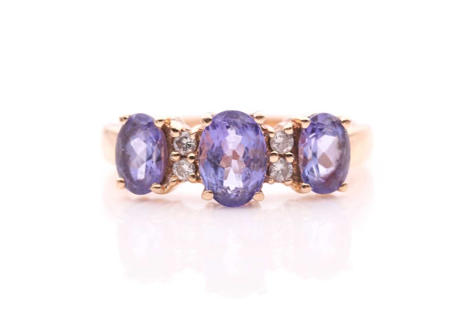 A yellow metal and tanzanite ring, set with three mixed oval-cut tanzanites, interspersed with