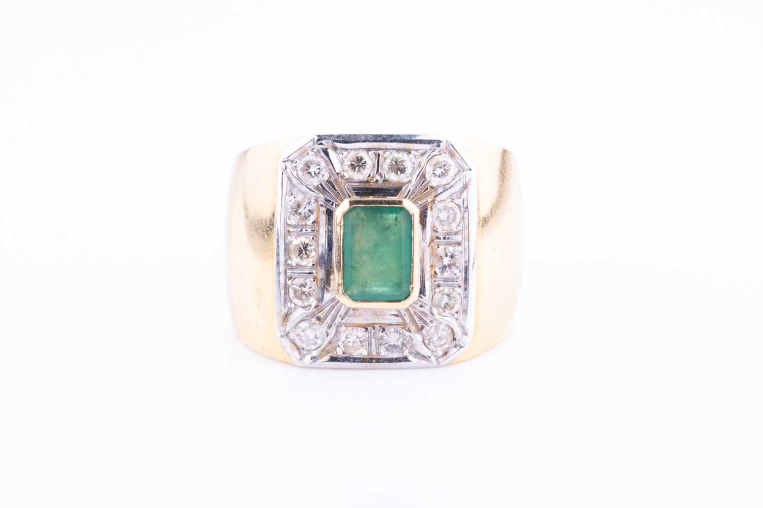 A yellow metal, diamond and emerald ring, centred with a bezel-set emerald, within a chamfered
