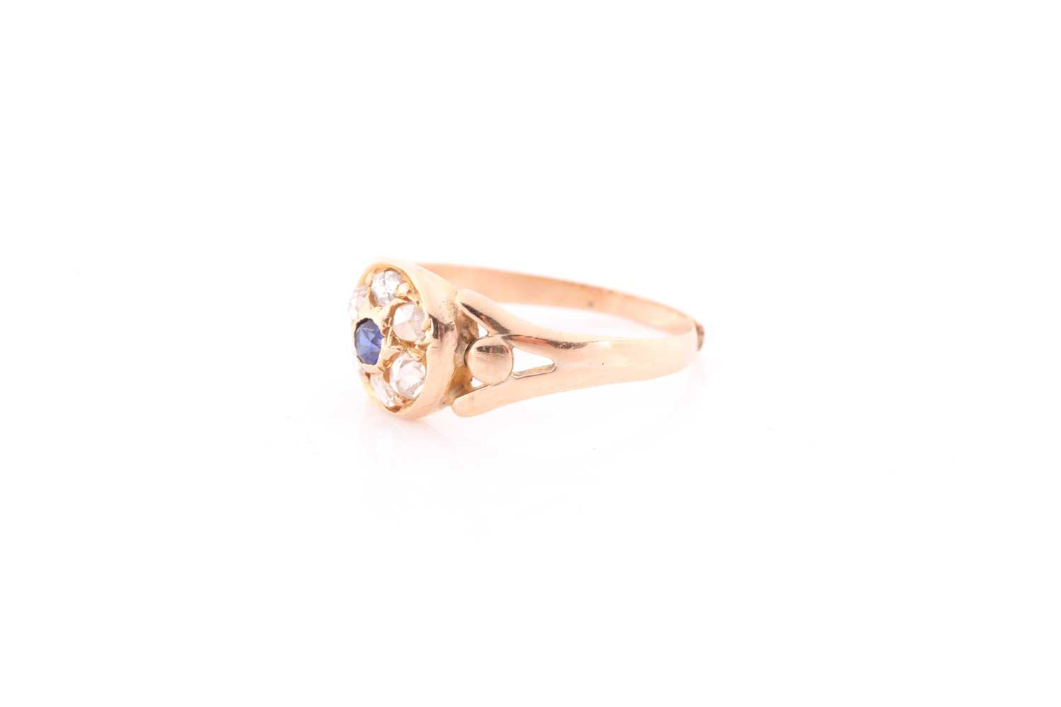A yellow metal, diamond, and sapphire ring, set with a small round sapphire, within a border of - Image 4 of 4