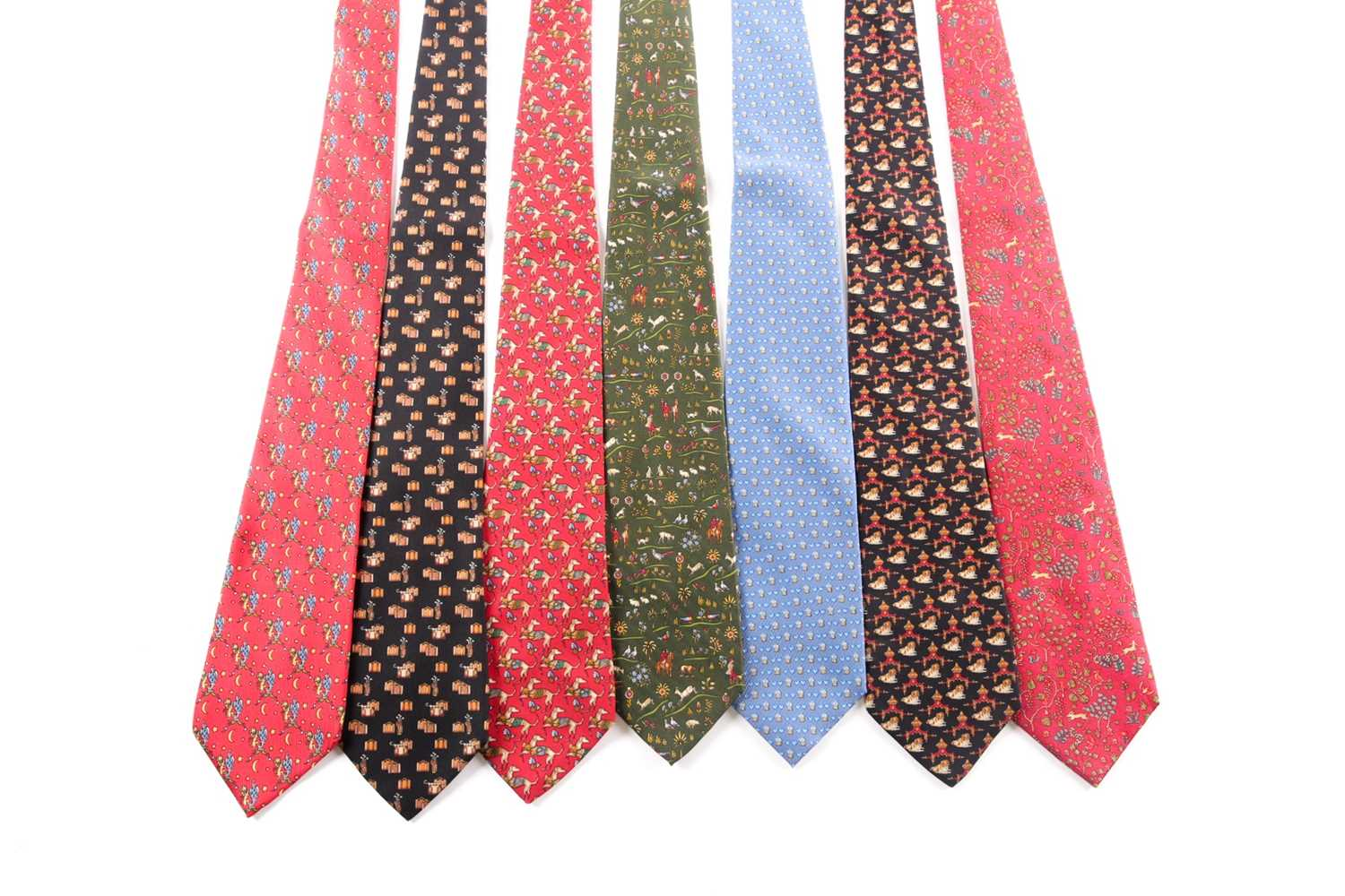 A group of seven Ferrogamo silk ties, various designs, in blue, red, green, and black silk. (7)