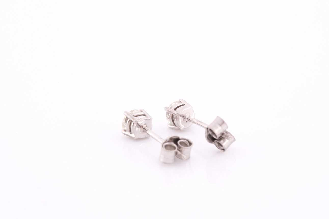 A pair of platinum and diamond earrings, the round brilliant-cut diamonds of approximately 0.67 - Image 4 of 4