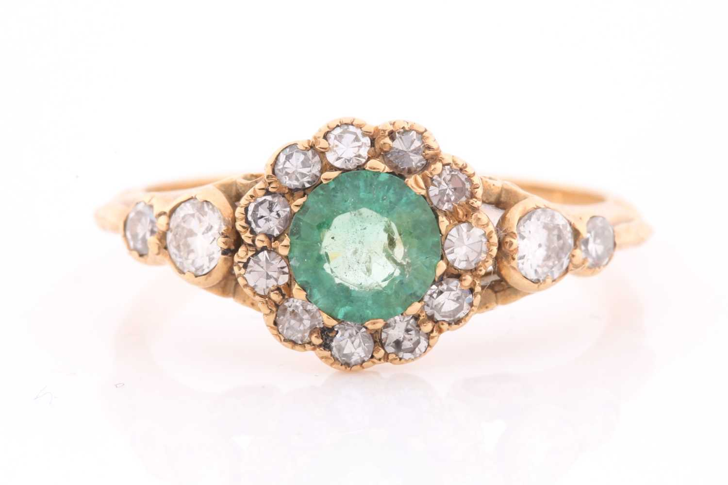 An 18ct yellow gold, diamond, and emerald ring, set with a mixed round-cut emerald, approximately