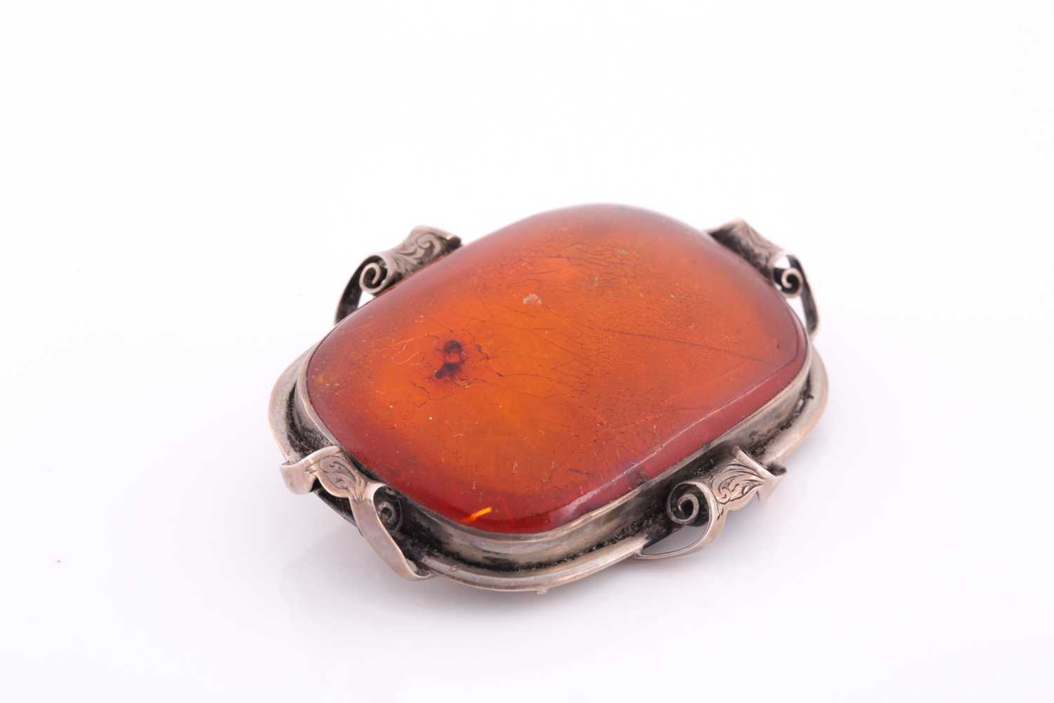An Art Nouveau silver and amber brooch, the large rectangular single stone amber plaque withing an - Image 2 of 3