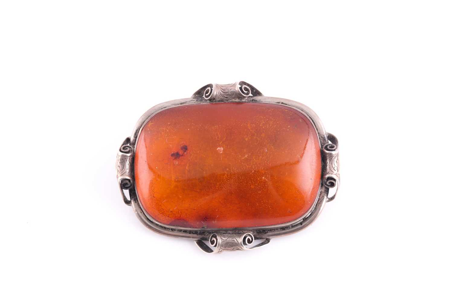 An Art Nouveau silver and amber brooch, the large rectangular single stone amber plaque withing an