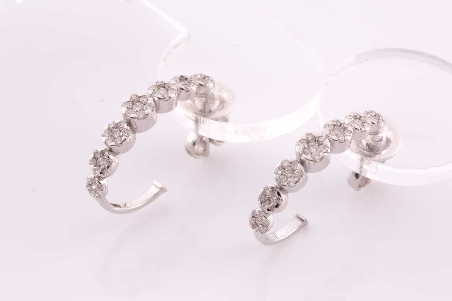 A pair of 18ct white gold and diamond earrings, each set with seven graduated floral clusters of - Image 2 of 3