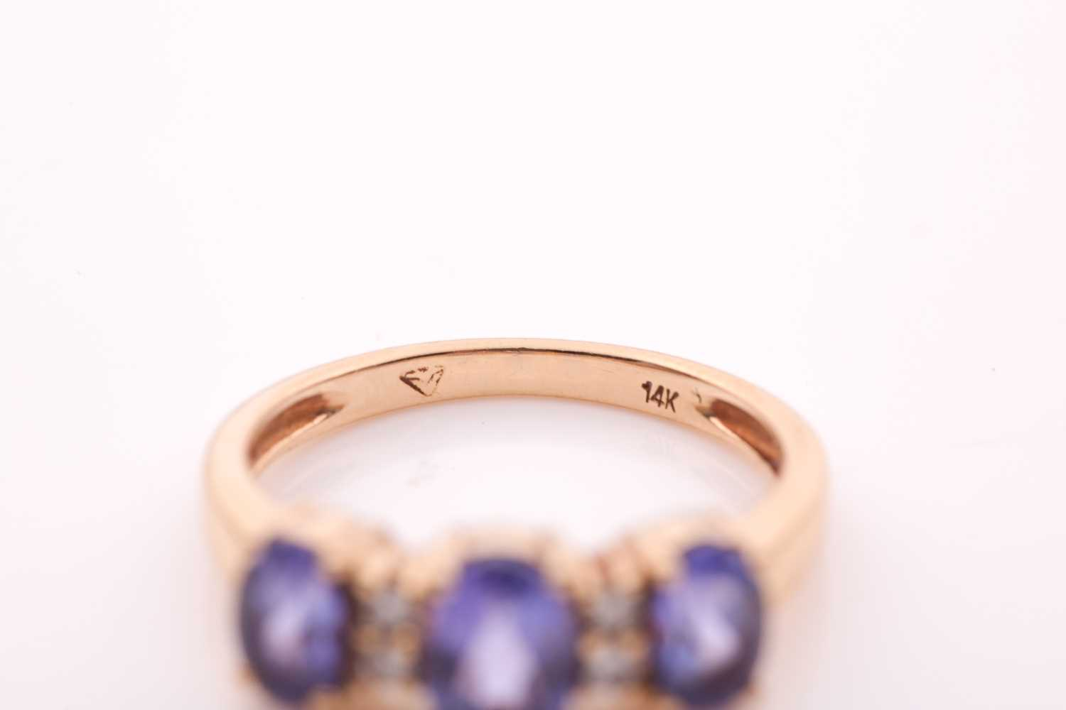 A yellow metal and tanzanite ring, set with three mixed oval-cut tanzanites, interspersed with - Image 2 of 5