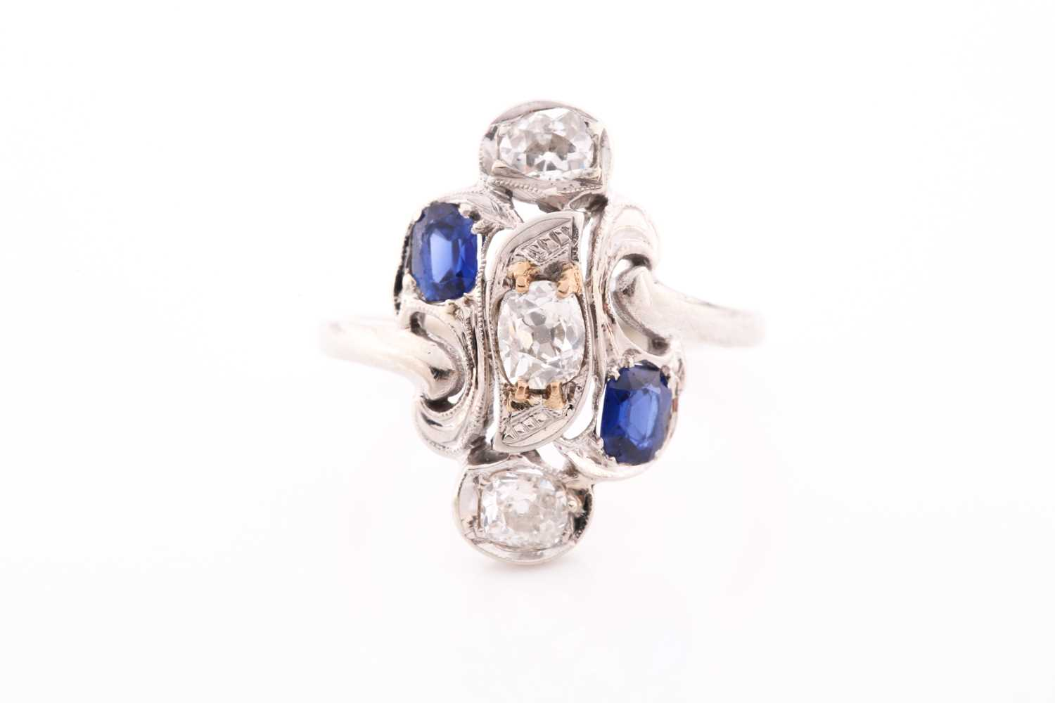 A diamond and sapphire ring, in the Art Nouveau style, the stylised mount inset with old Mine