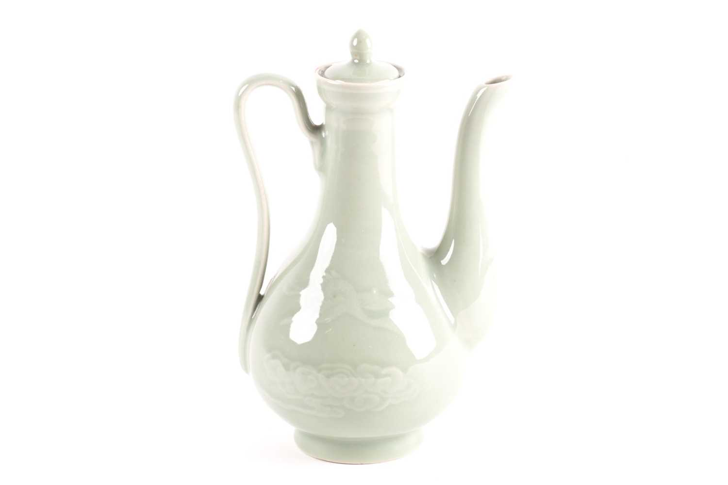 A Chinese celadon wine ewer, modelled in the Persian style, the long stopper with ball knop, moulded