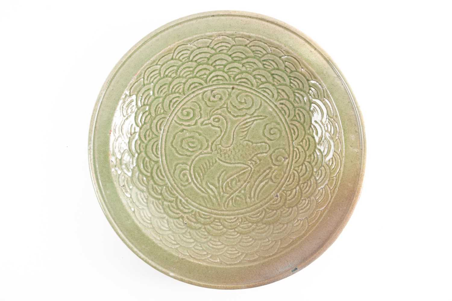 A circular celadon charger carved with a bird on a field of clouds within a stylized wave border