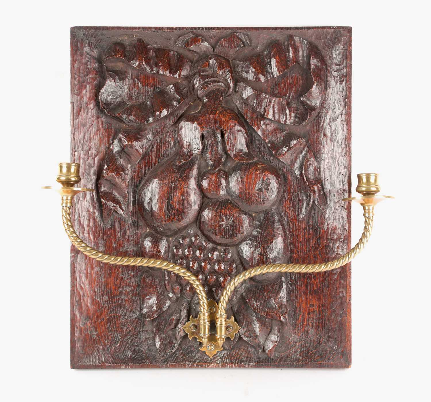 An English oak carved panel, late 19th century, carved with assorted fruits tied by a large
