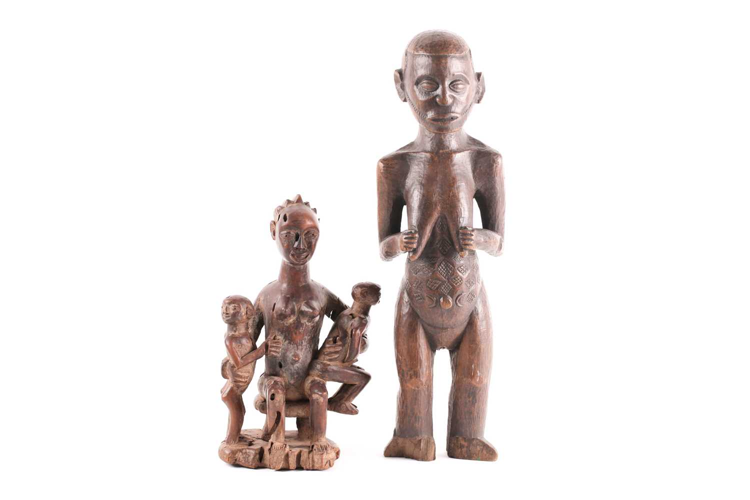 A Baule maternity figure, Ivory Coast, the smiling figure seated upon a stool and holding onto two