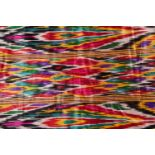 A brightly coloured rectangular Ikat style silk coverlet with cotton lining. 212 cm x 126