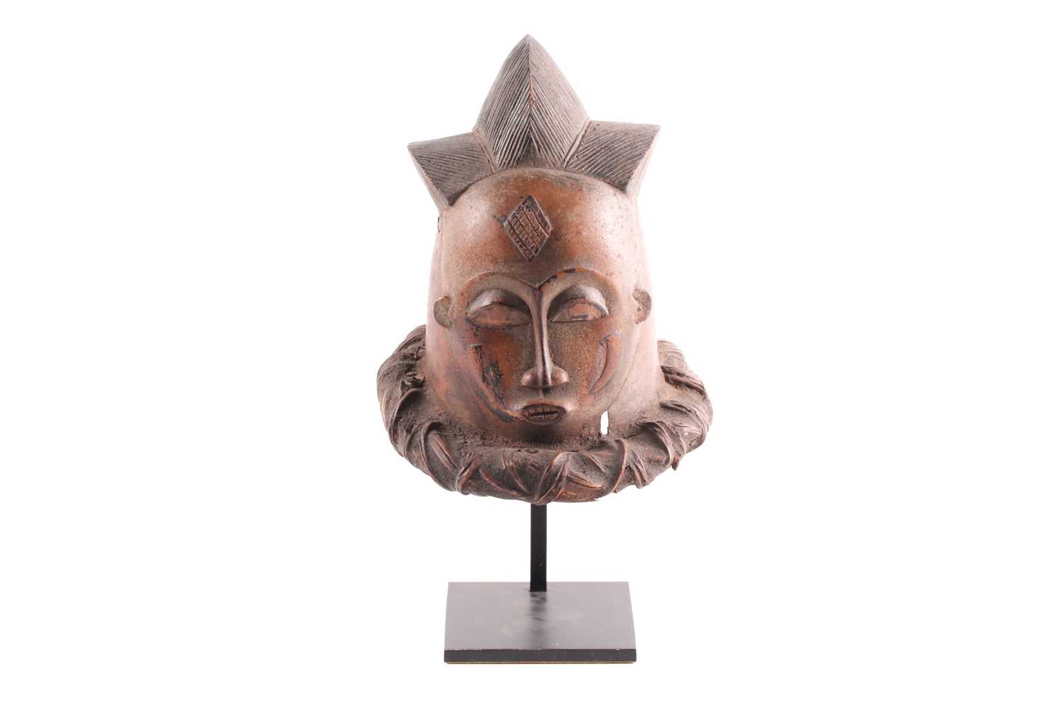 A small Baule helmet mask, Ivory Coast, the triple point coiffure with linear carving, with