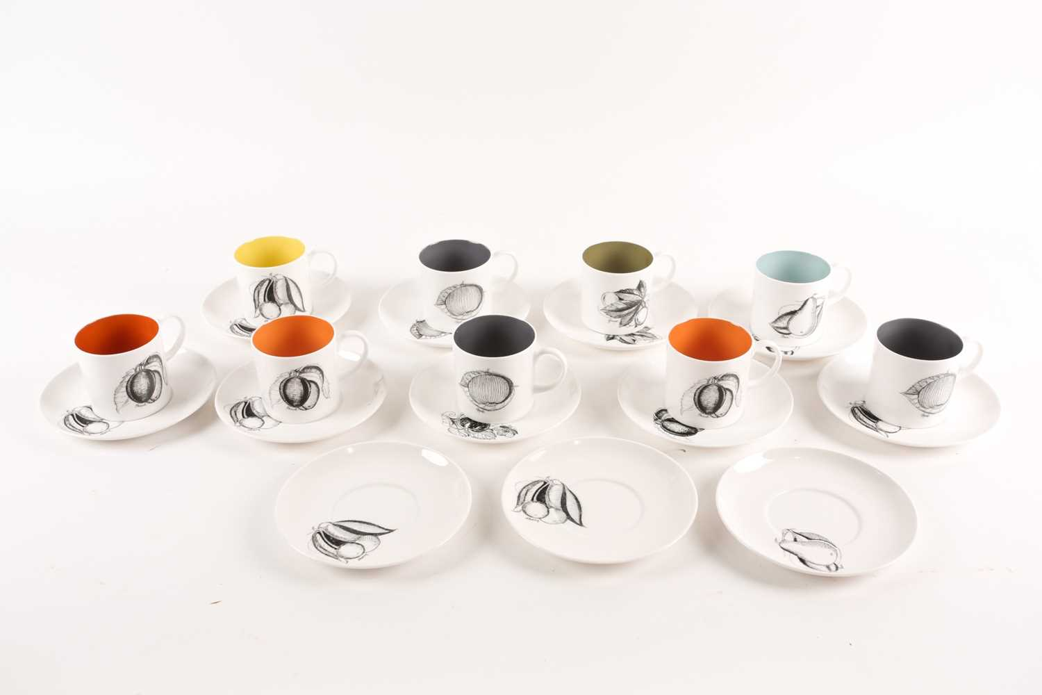 A collection of Susie Cooper black fruit pattern coffee cans and saucers, the cans with variously