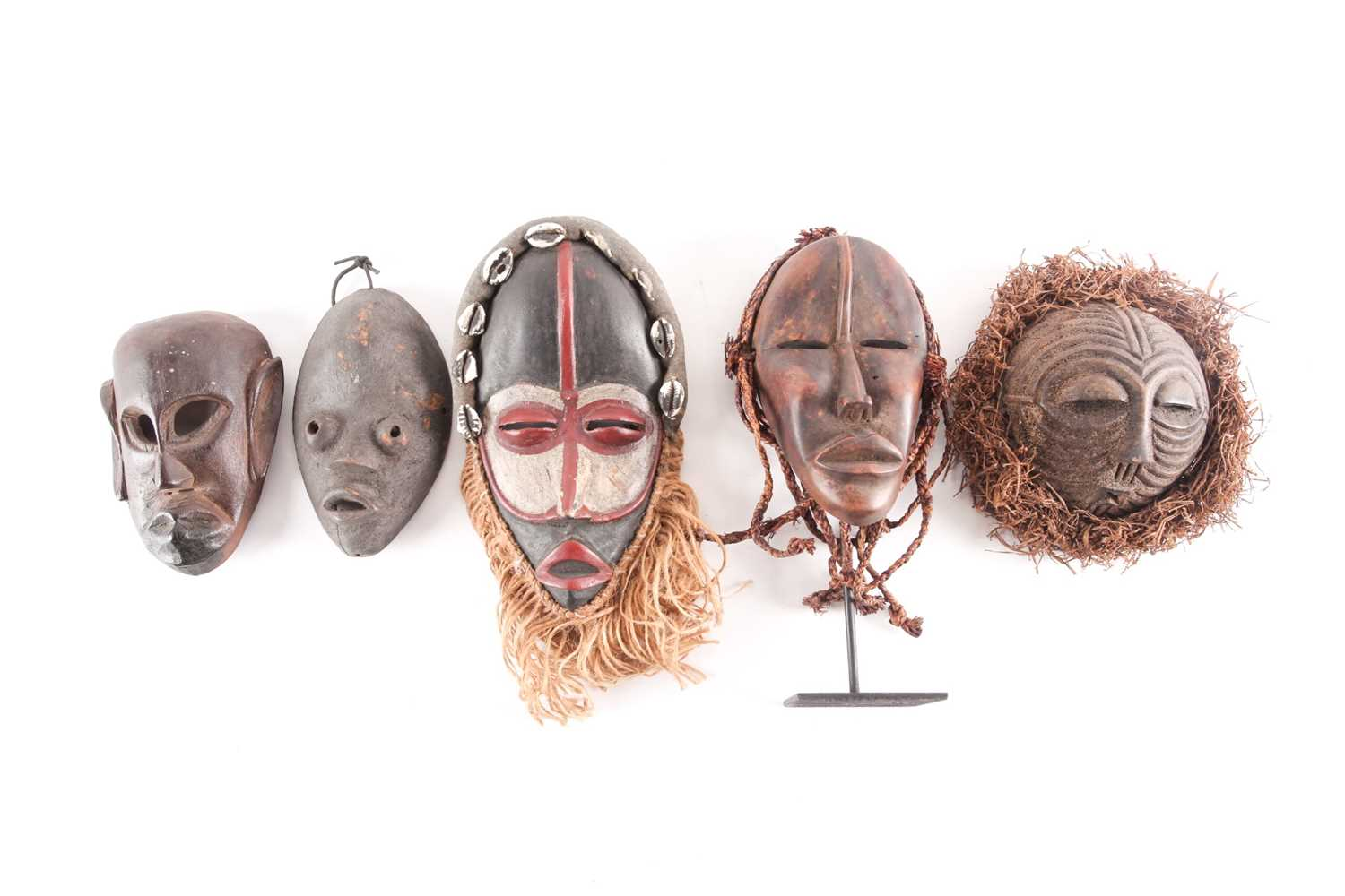Three Dan passport masks, Ivory coast, one with long woven natural fibres above a median line