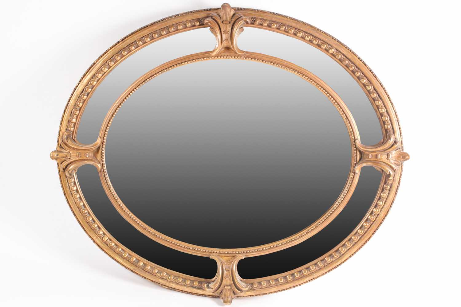 A Victorian carved wood and gilt gesso oval wall mirror with cartouch decoration and an outer border