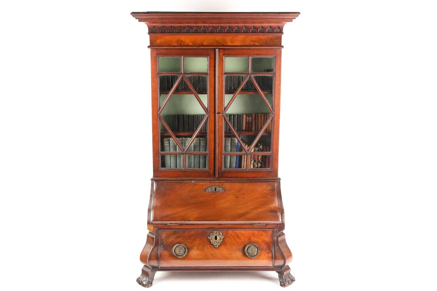 A Chippendale style miniature mahogany bombe bureau bookcase. The upper section with arcaded