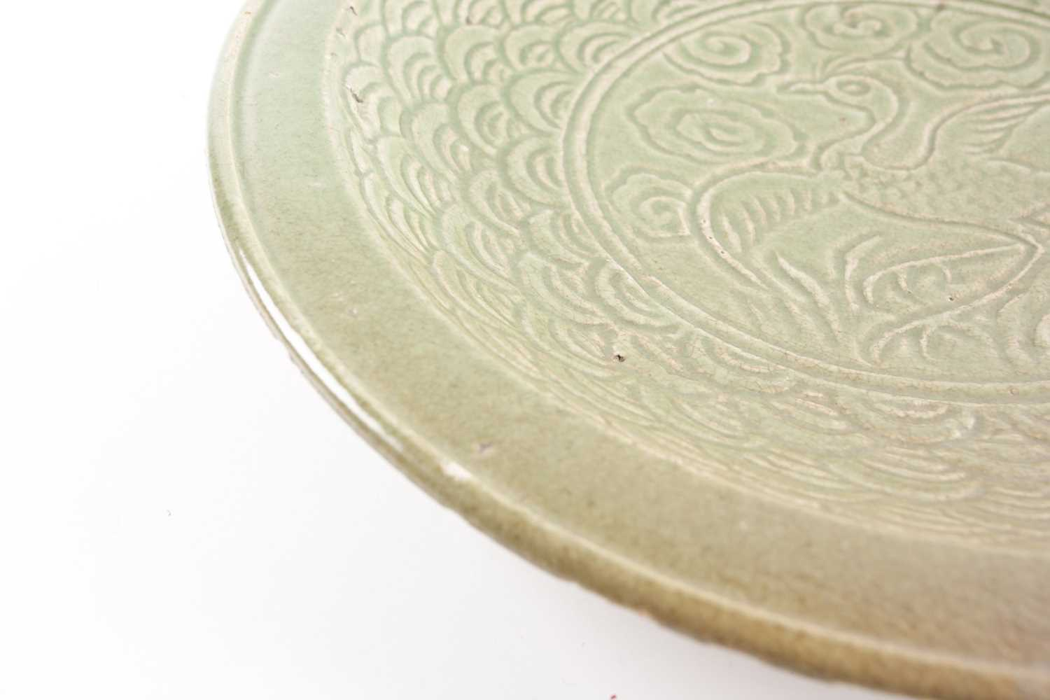 A circular celadon charger carved with a bird on a field of clouds within a stylized wave border - Image 5 of 5