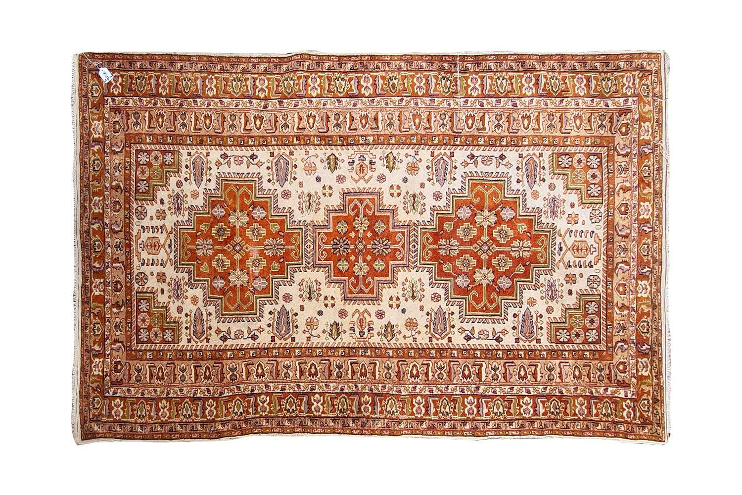 A 20th-century ivory ground Turkish rug with three rust coloured stepped cruciform lozenges within