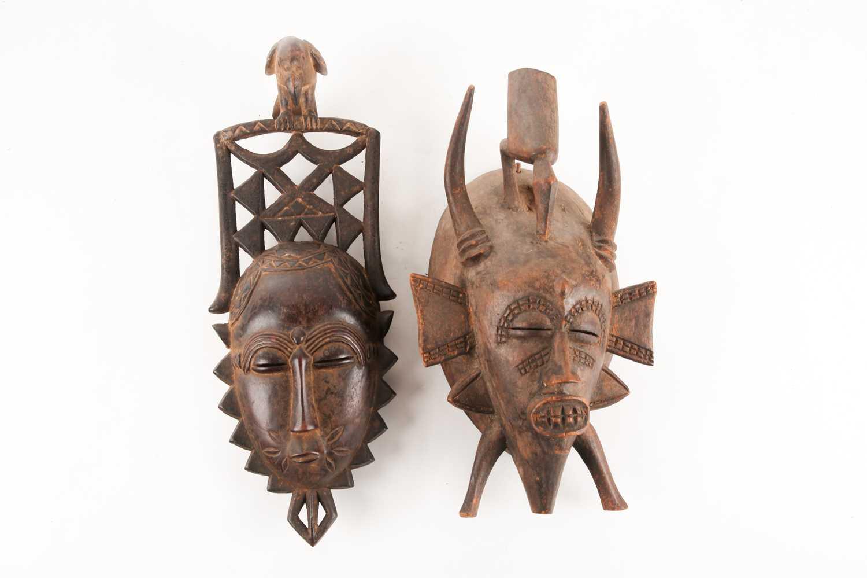 A Senufo Kpelie mask, Ivory Coast, with bird surmount and horns, 34.5cm; and a Yaure mask, Ivory