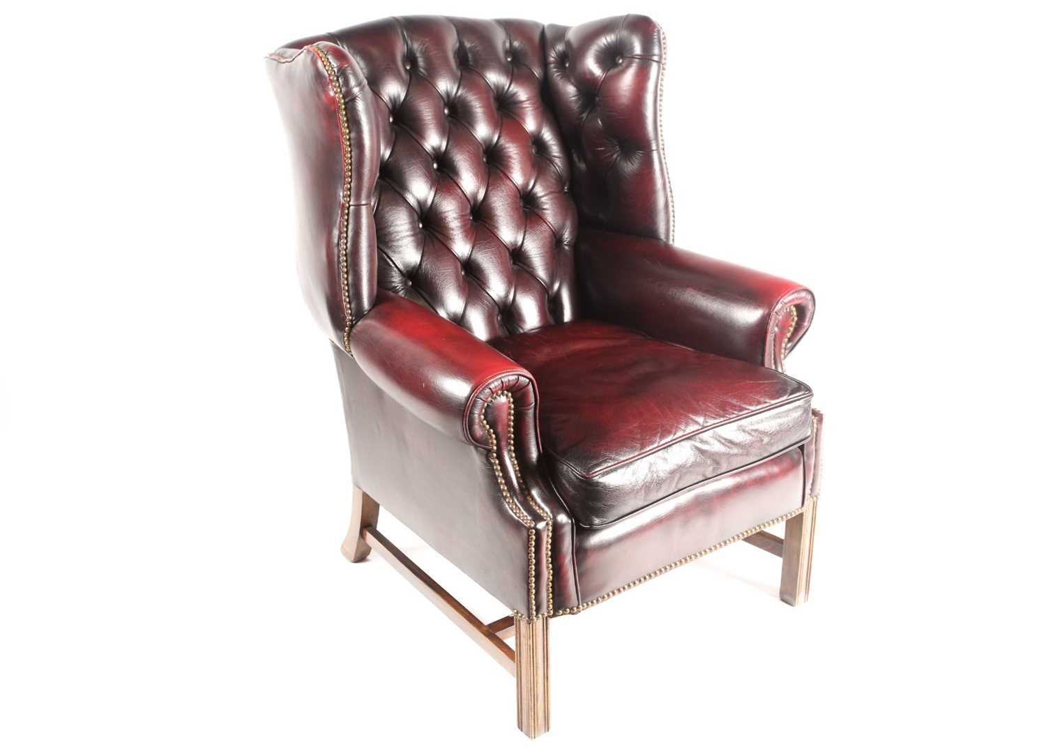 """A George III style deep button """"Ox Blood"""" hide upholstered hipped wing back fireside chair. With"""