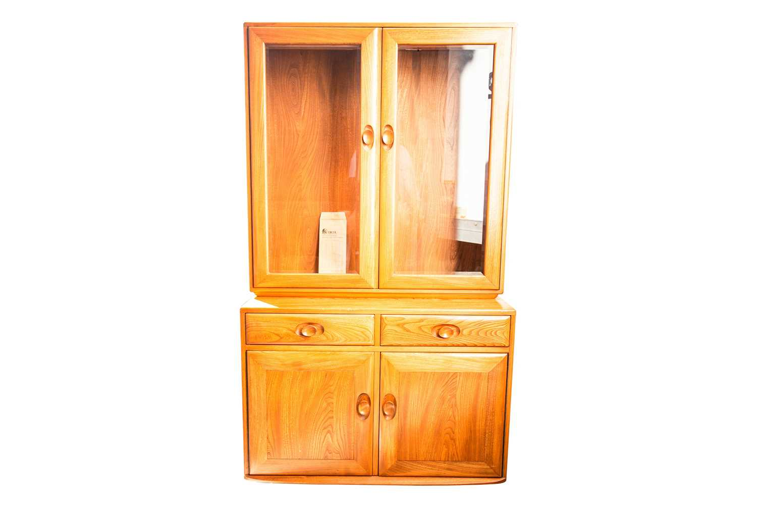 An Ercol golden dawn light elm two-section display cupboard. With two glazed doors above a base with