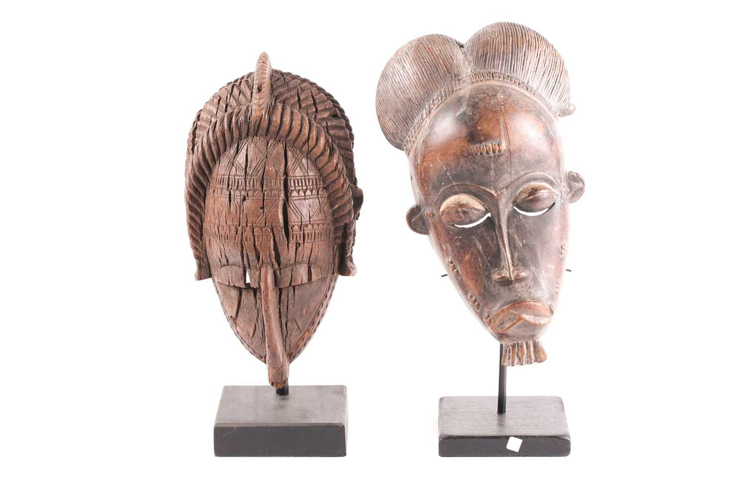 A Baule mask, Ivory Coast, with typical coiffure, relief carved scarifications to the face, the