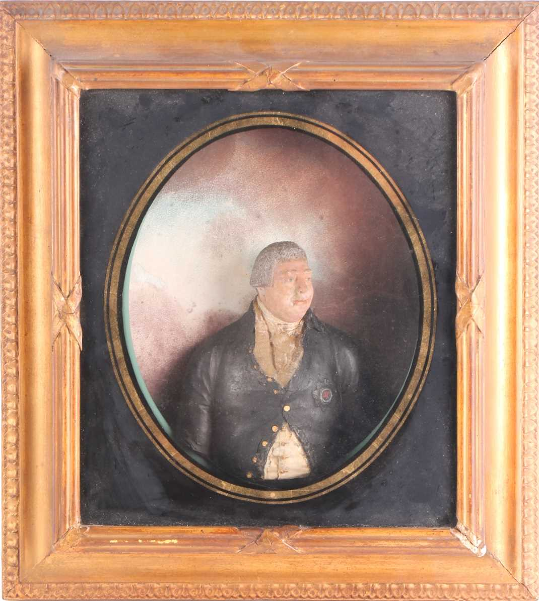 An 18th century painted relief wax half-length figure of George III, housed in a glazed gilt box
